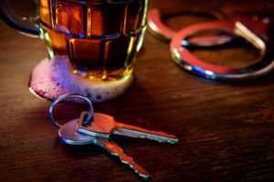 Car keys next to an alcoholic drink. Contact a Houston drunk driving accident lawyer after a wreck with a drunk driver.