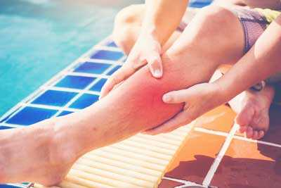 A man with a hurt leg by a swimming pool